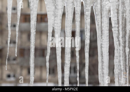 Dangerous icicles hang from the snowy roof of the house. Big icicles in the streets of the winter town. - Stock Photo
