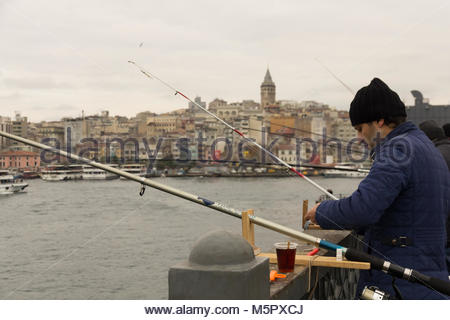 Istanbul, Turkey-December 12, 2015 -A close-up of a Turkish fisherman dressed in a blue winter jacket and a black - Stock Photo