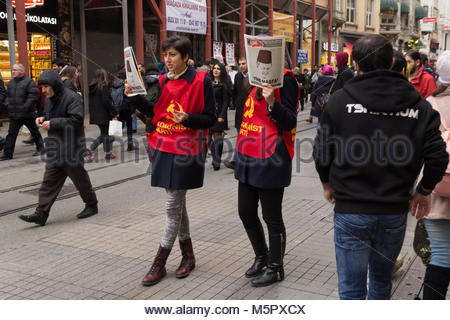 Istanbul, Turkey-December 12, 2015 -Two young women dressed in red clothes with agitation newspapers on the one - Stock Photo