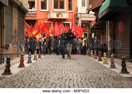 Istanbul, Turkey-December 13, 2015 -A pair of middle ages with background of Turkish demonstrators with red flags - Stock Photo