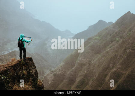Hiker with map in steep rocky terrain in front of a incredible panorama view of high mountain ranges deep ravines - Stock Photo