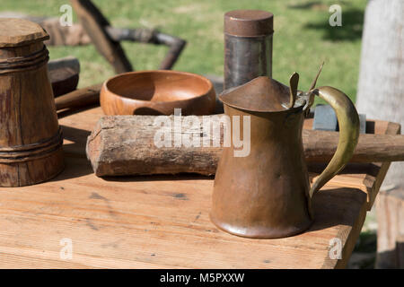 An old fashion copper beer tankard on a wooden table part of a display at an American revolution reenactment . - Stock Photo