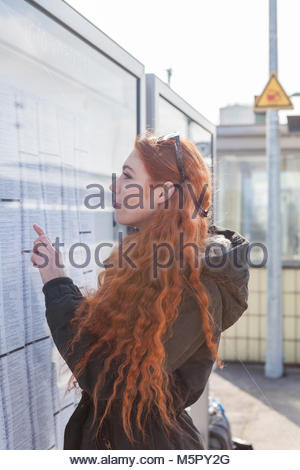 Woman at train station reads timetables - Stock Photo