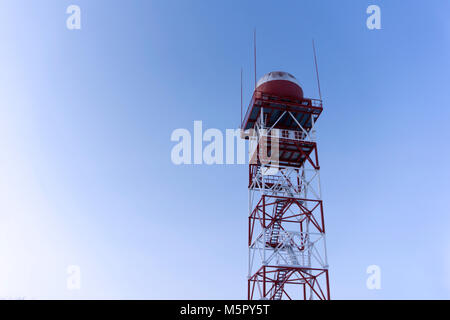 weather surveillance radar in a spherical protective dome, mounted on a trellis tower, against the sky - Stock Photo