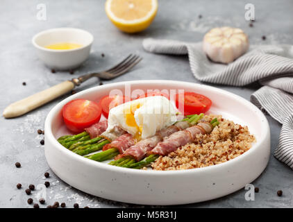 healthy breakfast. Baked asparagus with bacon, quinoa, egg poached in a white bowl on a gray stone background - Stock Photo