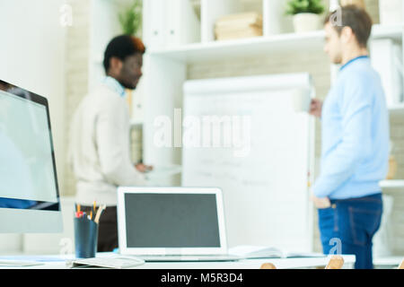 Two young interior designers standing at marker board and brainstorming on promising project while having working - Stock Photo