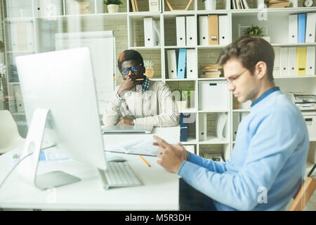 Working process in modern open plan office: multi-ethnic team of white collar workers sitting at desks and working - Stock Photo