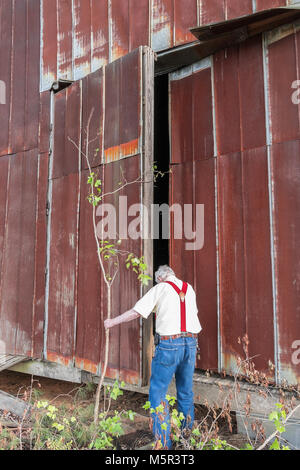 Man entering the gymnasium of a very old abandoned school. - Stock Photo