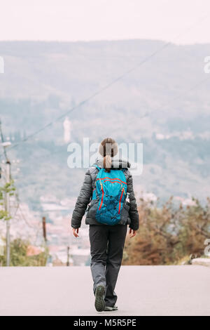 Tbilisi, Georgia. Young Woman Backpacker Traveller Walking Near Mountains In Autumn Day. Back View. - Stock Photo