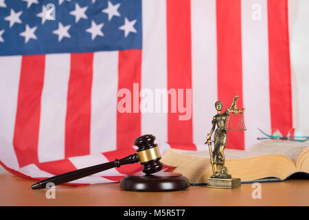 Statue of Themis and judge's gavel on a table. Flag of United States of America in the background. - Stock Photo
