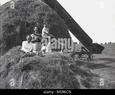 1937, historical picture, family enoying a rural holiday in the fresh air of Devon, England, having fun on a haystack - Stock Photo