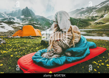 Woman relaxing in sleeping bag on red mat camping travel vacations in mountains Lifestyle concept adventure weekend - Stock Photo