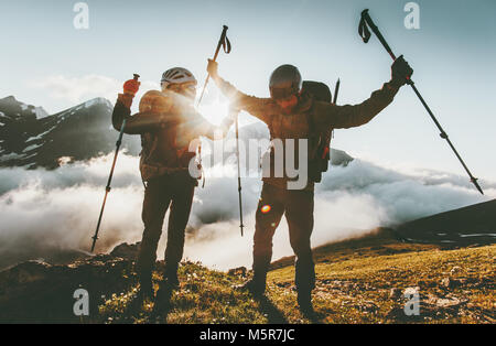 Happy travel couple man and woman on mountain summit love and adventure hiking Lifestyle wanderlust concept sunset - Stock Photo