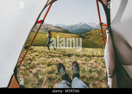 Camping couple traveling view from tent entrance woman walking in mountains man feet relaxing inside Lifestyle concept - Stock Photo