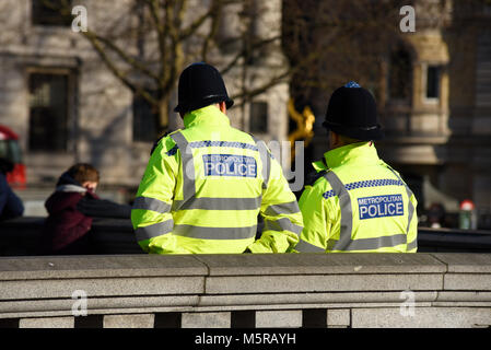 Metropolitan police officers in Trafalgar Square, London watching over members of the public. Space for copy - Stock Photo