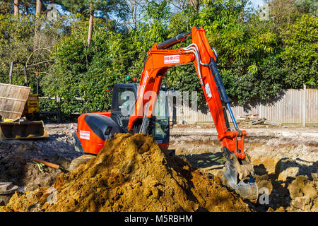 Large orange heavy plant mechanical digger parked on a construction site after digging excavations for foundations - Stock Photo