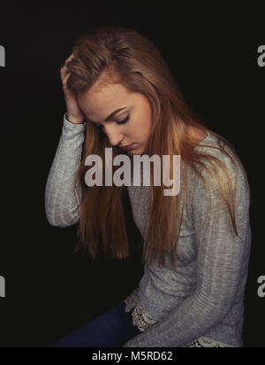 Teenage girl with long blond hair sitting looking sad. - Stock Photo