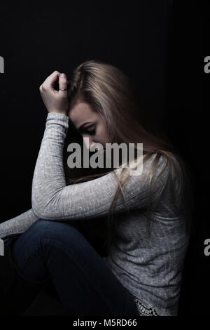 Teenage girl sitting in profile in the shadows with one hand to her head. - Stock Photo