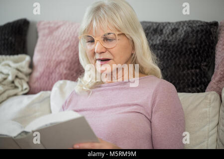 Portrait of senior lady at home reading book intently - Stock Photo