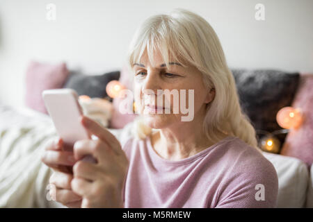Portrait of senior lady using smartphone sitting at home - Stock Photo
