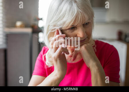 Portrait of pensive senior lady listening to phone conversation intently - Stock Photo