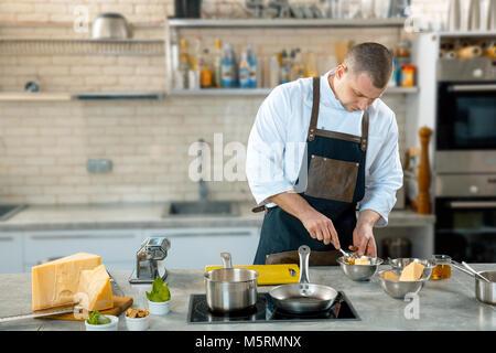 A chef in a process - preparing Italian dish. Kitchen interier - Stock Photo