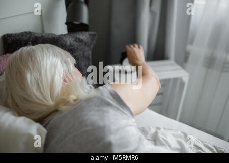 Back portrait of senior woman lying in bed turning off alarm clock - Stock Photo