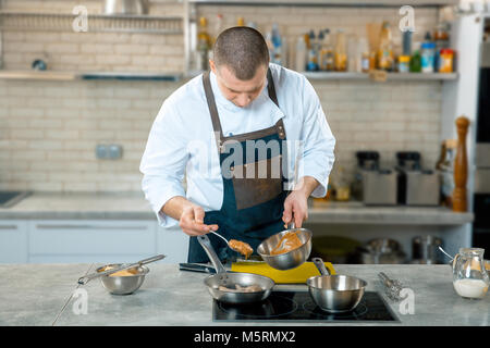 Chef cook pours sauce into a frying pan. Fast food dinner and lunch restaurant bar. Kitchen interior - Stock Photo
