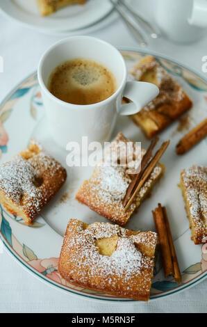 Coffee mug with apple cinnamon cake pieces on white background - Stock Photo