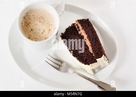 Cup of coffee with one piece chocolate cake and dessert fork on white background - Stock Photo