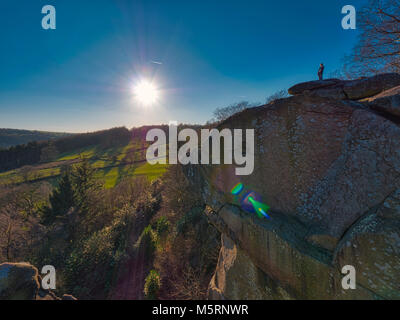 Peak District, Derbyshire, UK. 25th February, 2018. UK Weather man admiring the cold clear blue sky's & spectacular view from the top of Cratcliffe Tor, with a gritstone rock face below him in the Peak District National Park, Derbyshire, UK Credit: Doug Blane/Alamy Live News