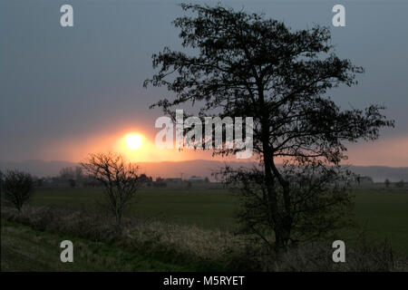 Burscough, Lancashire. 26th Feb, 2018. UK Weather.UK Weather. Sunrise through the dark clouds with snow showers - Stock Photo