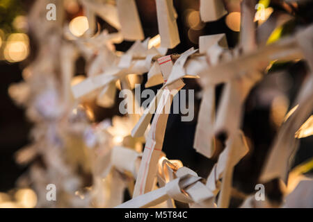 Close-up view Group of Omikuji, a fortune telling paper strip, tied on the ropes with blurred background. People - Stock Photo