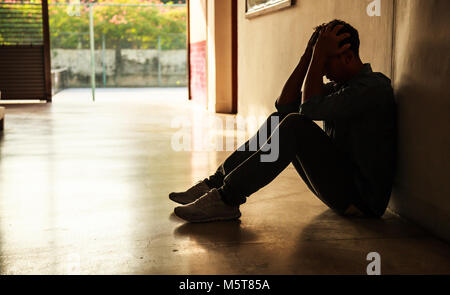 Emotional moment: man sitting holding head in hands, stressed sad young male having mental problems, feeling bad, - Stock Photo