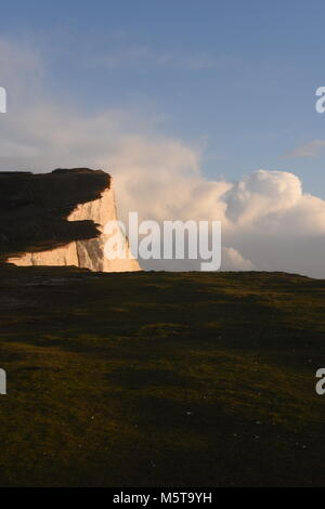 Beautiful Seven Sisters chalk cliffs with a golden glow from a sunset and dramatic clouds- taken from the beach - Stock Photo