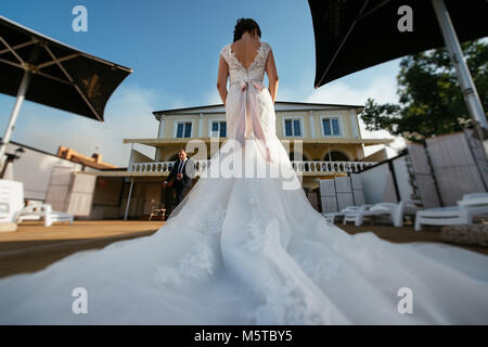 Back view of bride in luxury wedding dress with train waiting for ...