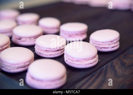 Pink macarons on wooden table - Stock Photo