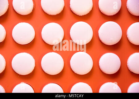 Pink macarons on orange background - Stock Photo