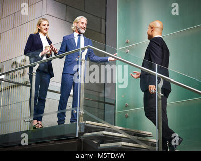 senior corporate executive welcoming visitor on stair of modern office building, low angle view. - Stock Photo