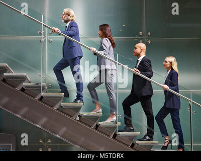 multinational and multiethnic corporate business people male and female walking up stairs in a line in modern office - Stock Photo