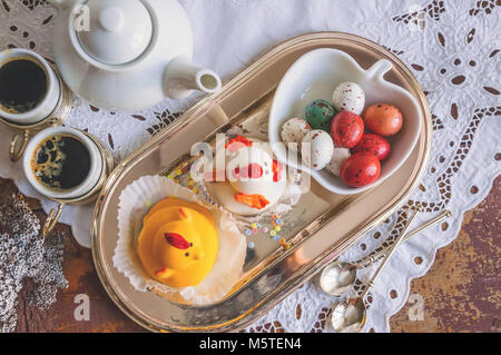 Figures from marzipan in the form of white and yellow chickens on Easter table with coffee cups and pastry eggs - Stock Photo