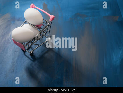 White eggs in a shopping cart, perfect Easter sale, deal, promotional background. - Stock Photo