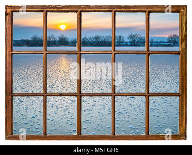 sunset over frozen lake in Colorado as seen through vintage sash window with dirty glass - Stock Photo