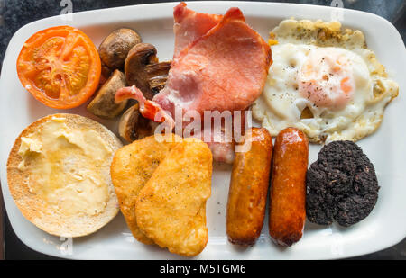 Full English breakfast fried egg, bacon, baked beans, white muffin, black pudding, grilled tomato, sausages, mushrooms - Stock Photo