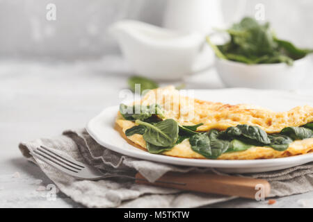 Omelette stuffed with spinach and cheese for a breakfast. - Stock Photo