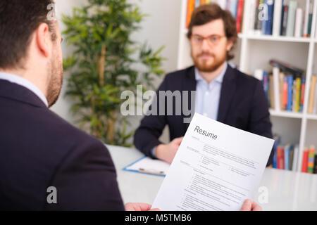 Recruiter reading curriculum during job interview - Stock Photo