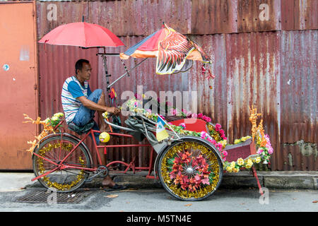 PENANG, MALAYSIA, NOV 12 2017, a traditional tricycle in the streets of Penang. A driver decorated rickshaw waits - Stock Photo