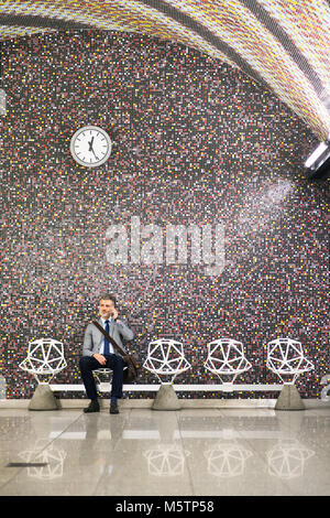 Mature businessman with smartphone in a metro station. - Stock Photo