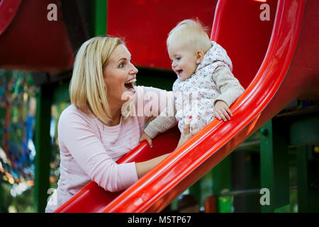 Little girl and her beautiful young mother playing on the playground - Stock Photo