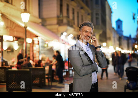 Mature businessman with a smartphone in a city. - Stock Photo